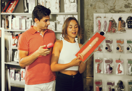 adult spanish woman and man bayers choosing long rubber phallus in the shop