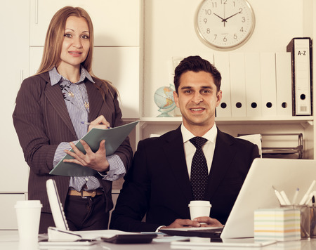 Attractive secretary helping boss and writing instructions at workplace in office