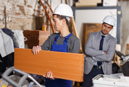 Strict  male chief supervising quality of work of employee at building Stock Photo