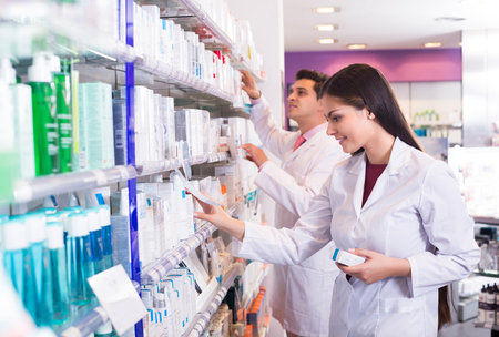Young pharmacist and pharmacy technician posing in drugstore