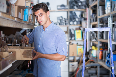 young man chooses small details in boxes in a building store