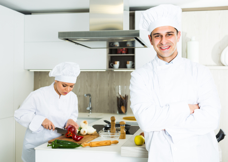 Young male chef  in white uniform standing near workplace on kitchen 写真素材