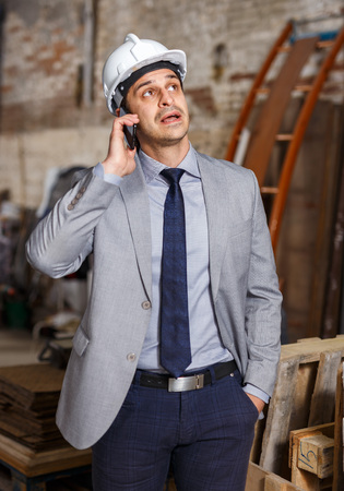 Unhappy male architect talking on phone during supervising building