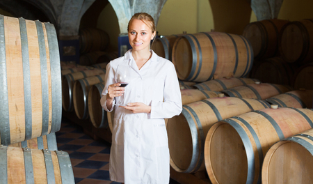 Young blonde woman in white robe checking ageing process of red wine Reklamní fotografie