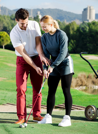 Cheerful male golf trainer showing female player how to hit ball rightly
