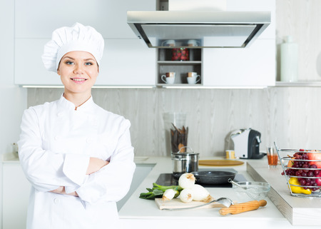 Young female chef  in white uniform standing near workplace on kitchen