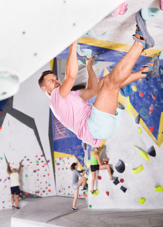 Confident male mountaineer climbing a artificial rock wall without the belay indoors Reklamní fotografie