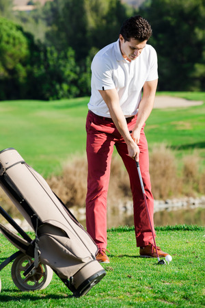 Attractive male golf player getting ready to hit ball at golf course