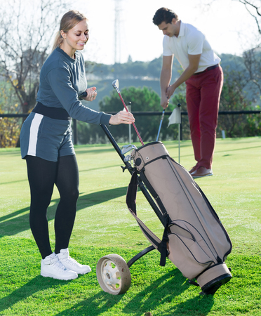 happy woman golfer deciding on right club while her male partner hitting ball