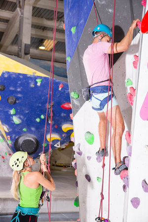 Sporty couple of climbers dressed in a rock climbing outfit training at a bouldering gym