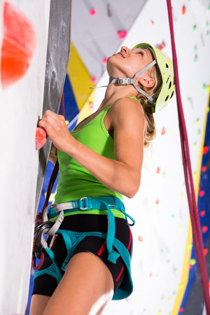 Sporty young woman dressed in rock climbing outfit training at bouldering gym