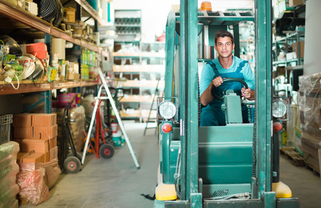 calm man in unifom is using сargo moving machine in the warehouse building store