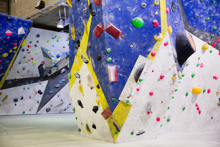 Multicolored bright painted  climbing wall for training at modern bouldering gym Stock Photo