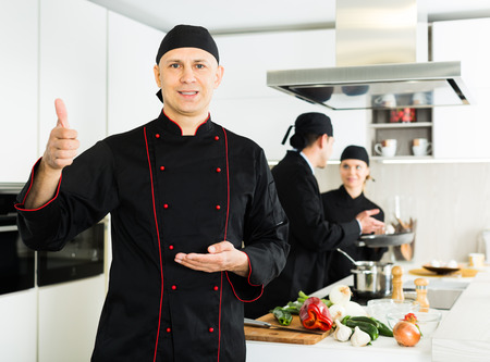 Professional chef  in black uniform standing  near workplace on kitchen 免版税图像