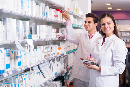 Smiling pharmacist and pharmacy technician posing in interior
