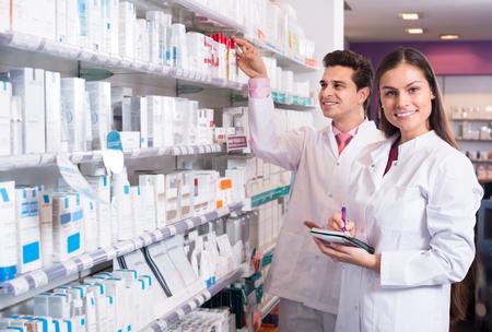 Sonriente farmacéutico y técnico de farmacia posando en interior Foto de archivo