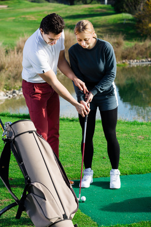 Sporty trainer is showing young female golf player exercises for accuracy hits.