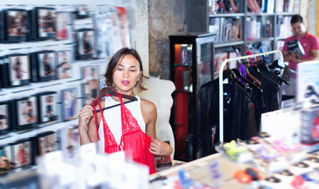 Glad  smiling adult female purchaser touching sexy red clothes in the modern sex shop Фото со стока - 121964563