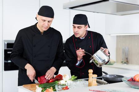 Professional men chefs  in black uniform working together on kitchen