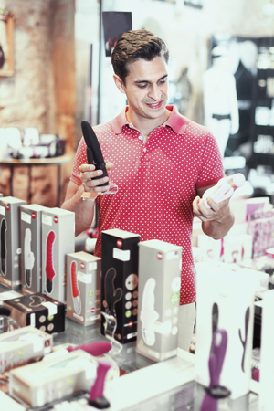 Glad cheerful smiling male purchaser touching toys in the modern shop