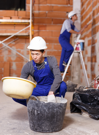 Asian and Hispanic workers in work wear doing repair work inside built cottage Stock Photo