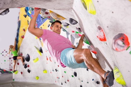 Smiling cheerful  glad male alpinist practicing indoor rock-climbing on artificial boulder without safety belts Reklamní fotografie