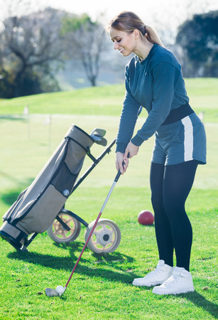 Young american woman preparing to hit ball at golf course