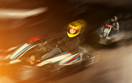 Young woman in helmet and other people driving cars for karting in sport club indoor Фото со стока