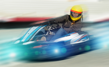 Portrait of girl in helmet driving kart at a racing track outdoors