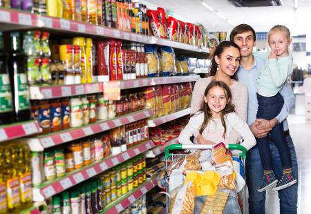 Padres jóvenes sonrientes con dos hijas juguetonas comprando comida en hipermercado