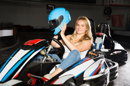 Smiling woman with helmet sitting in car for karting in sport club
