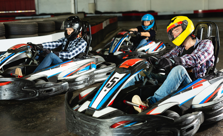 active man and women competing on racing cars at kart circuit
