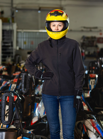 Happy cheerful positive smiling young woman in yellow  helmet at kart circuit
