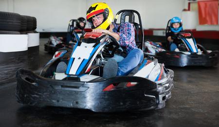 Portrait of adult man driving racing car at kart circuit