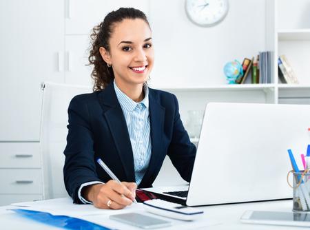Señora de negocios agradable positivo sentado en el escritorio de oficina con portátil