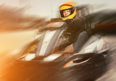 Portrait of girl in helmet driving a kart at racing track outdoors