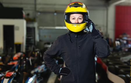 Glad woman in helmet standing near sport cars for karting in sport club