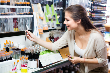 happy young brunette woman selecting brushes for painting in art department