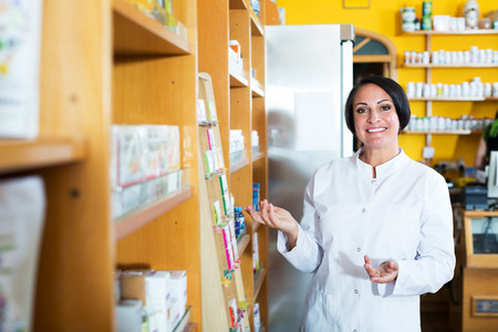Portrait of cheerful mature pharmacist woman in biologically active dietary supplements store