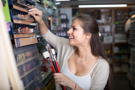 Young smiling woman customer shopping various pencils in art store Фото со стока