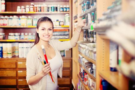 Portrait de jeune femme gaie choisissant la couleur de la peinture dans le tube dans la boutique d'art