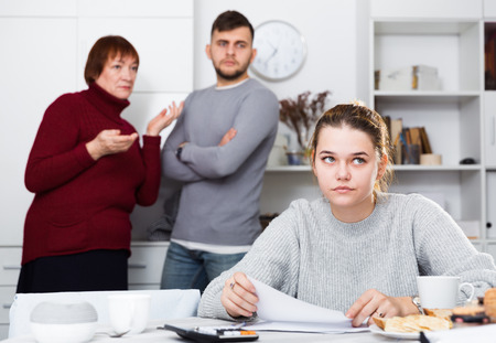 Portrait of distressed girl with paperwork at home table with irritated family behind her Фото со стока