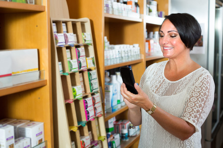 joyful smiling mature brunette woman looking at her phone while shopping in drugstore