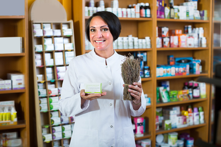 pharmacist in uniform holding bunch of dried herbs in pharmaceutical store Stock fotó