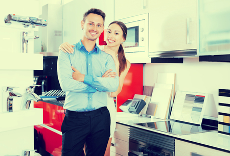 Pair of young glad people standing in furniture accessories store