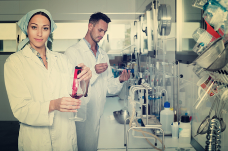 Young female professional in white coat  testing wine in chemistry lab