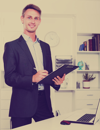 portrait of young smiling man in formal wear holding clipboard in hands in office