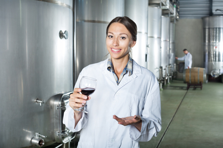 Smiling young woman wearing uniform standing with glass of wine in fermenting section on wine factory