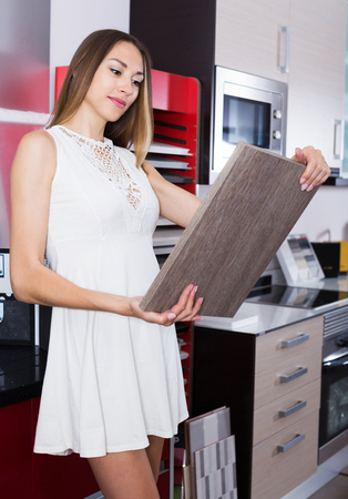 Smiling adult girl choosing kitchen fronts materials for her apartment