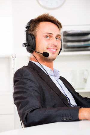 Cheerful young man talking using hands-free set at customer service office